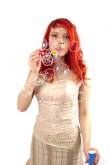 pretty young girl blowing soap bubbles