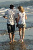 couple walking on waters edge at beach poster