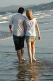 couple walking along beach poster