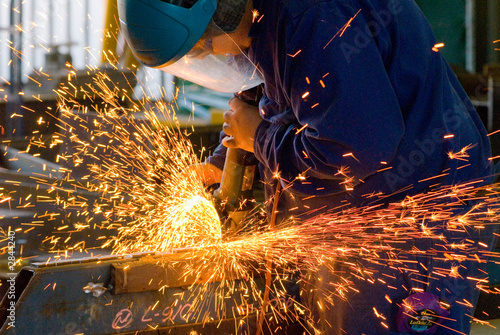 men at work grinding steel