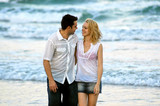 couple strolling along the beach poster