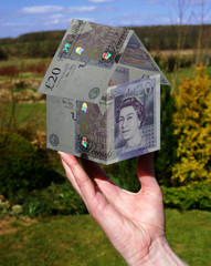 hand holding £20 house