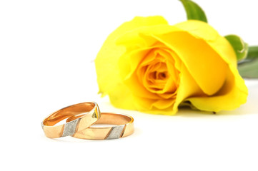 wedding rings and yellow rose at the background