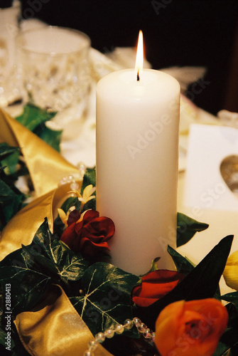 lit candle decoration with orange and red roses