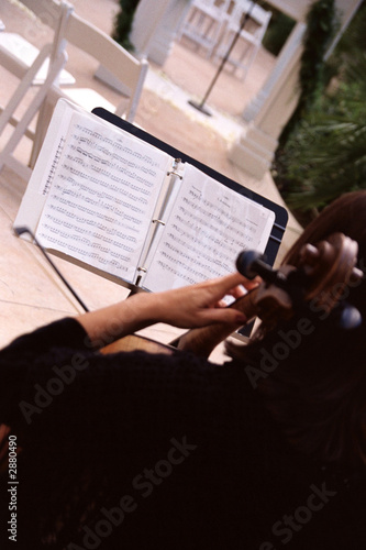violin player with music sheets outdoors