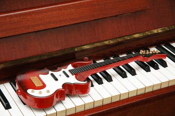 musical concept - rock guitar on the piano keys