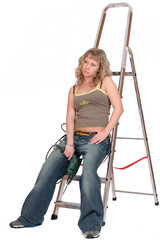 young woman with a drill on stepladder