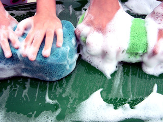 hands with soapy sponges