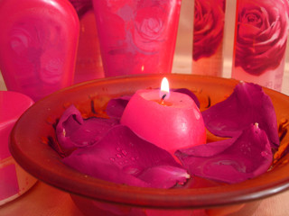 spa essentials (red rose petals on water with candle, cream and