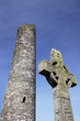 irish cross in front of a monastic round tower
