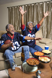 middle-aged african-american couple watching sports on tv.