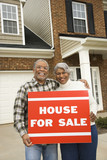 middle-aged couple holding a for sale sign. poster