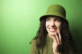 caucasian woman wearing green clothing and hat. poster