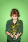 caucasian woman looking at plant. poster