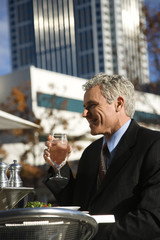 businessman drinking water at table.