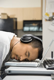 man with headphones sleeping on laptop. poster