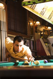 young man preparing to hit pool ball. poster