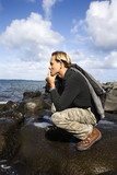 man kneeling by the coast of maui, hawaii. poster