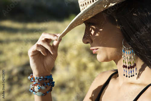 young woman tipping a cowboy hat.