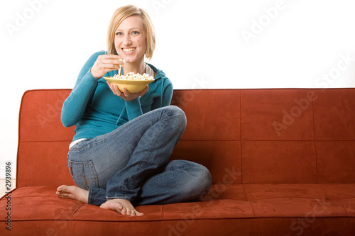 young woman eating popcorn on a red couch