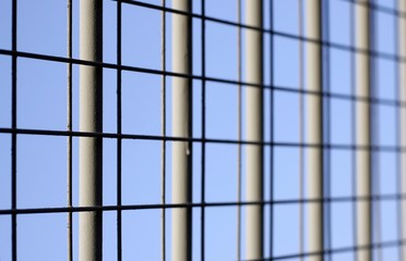 closeup of iron fencing over blue sky