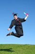 male graduate leaping for joy outdoors