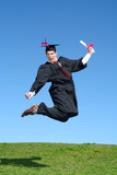 male graduate leaping for joy outdoors poster