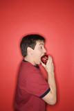 caucasian teen boy biting apple. poster
