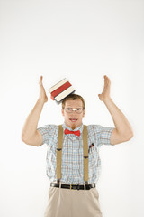 young man with books sliding off head.