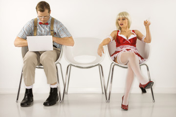 young man sitting with laptop with young  woman looking at him.