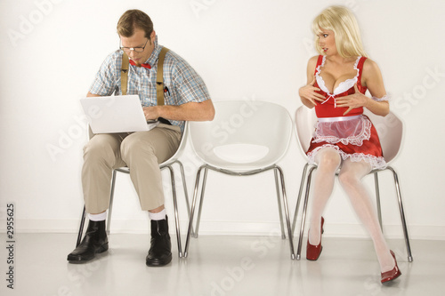 young man sitting with young  woman distracting him with cleavag