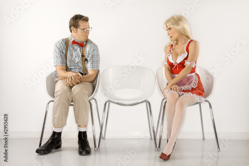 young man and young  woman sitting and looking at eachother.