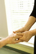 middle-aged female massaging elderly male's hand.