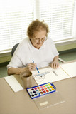 elderly caucasian woman painting with watercolors. poster