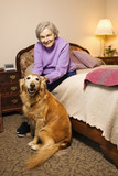 elderly caucasian woman in bedroom with dog.