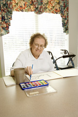 elderly caucasian woman painting with watercolors.