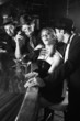 retro female sitting at bar surrounded by men.