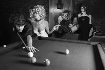 retro male shooting pool with three retro females watching.