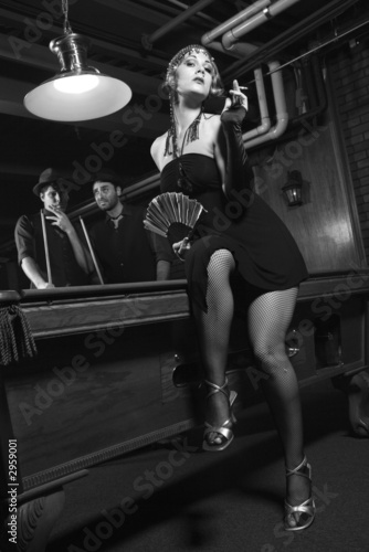 retro female in front of pool table with two  men in background.