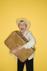 woman grasping suitcase.