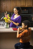 Pregnant mom arranging flowers while son eats breakfast. poster