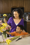 Pregnant mother and son arranging flowers. poster