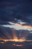 Sunbeams coming through clouds at sunrise. poster