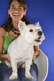 Woman holding white terrier dog. poster