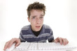 confused teenage boy using computer