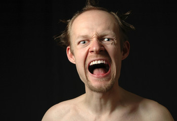 crazy angry man shouting on black background