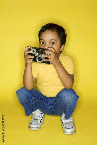 Male child kneeling with camera.
