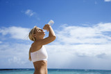 Woman drinking water on beach.