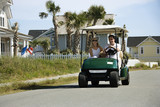 Dad driving golf cart with mom beside him. poster