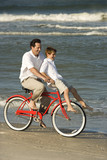 Dad riding bike with son on handlebars. poster